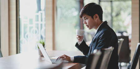 Young professional businessman drinking a cup of coffee while working with laptop in office room Banco de Imagens