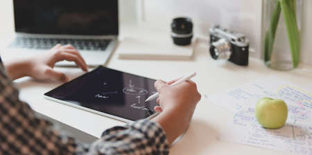Professional male designer drawing the mind mapping on tablet in minimal office room
