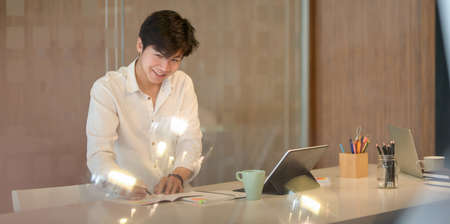 Cheerful young businessman working his project with laptop computer in modern workplace