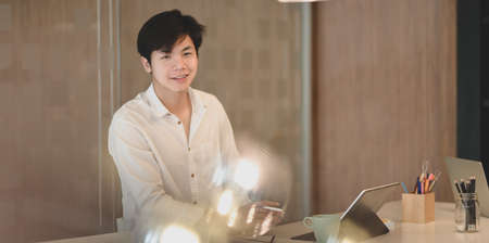 Cheerful young businessman working his project with laptop computer and smiling to the camera