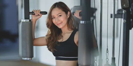 Close-up of beautiful Asian woman with tan and slim body exercise on machine in the gym Stock Photo