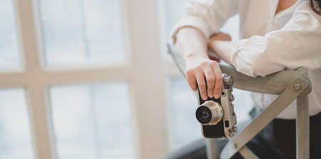 Cropped shot of young beautiful photographer holding camera while sitting on the chair in her modern workplace