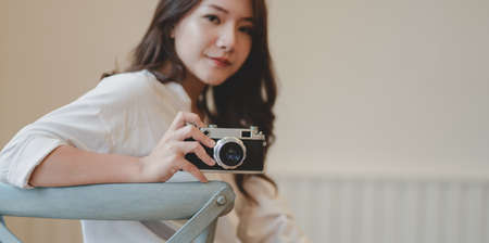 Young beautiful photographer holding camera and smiling at the camera while sitting on the chair in her modern workplace