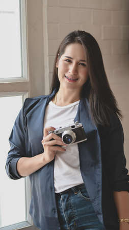 Portrait of beautiful professional photographer holding camera and smiling to the camera