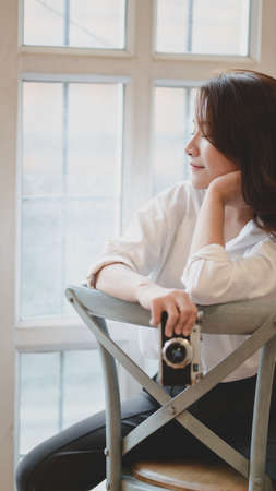 Young beautiful photographer holding camera while sitting on the chair in her modern workplace 스톡 콘텐츠