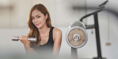 Fit asian athletic woman lifting weights inside the gym and smiling at the camera, muscular building concept