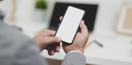 Close-up view of businessman holding blank screen smartphone in his modern office room.