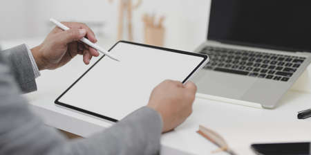 Close-up view of businessman writing his plan on blank screen tablet in his modern office room