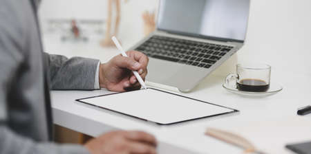 Cropped view of professional businessman working on his project while writing on blank screen tablet in modern office room Stock Photo