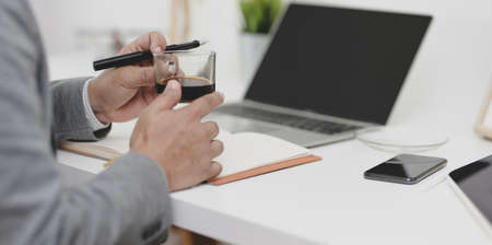 Close-up view of young professional businessman holding a cup of coffee while working on his project in modern office room