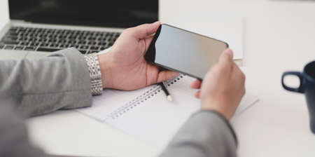 Close-up view of businessman holding blank screen smartphone in his modern office room Stock Photo