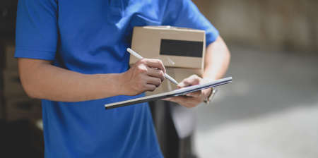 Professional delivery man working with parcel box while checking customer order on tablet.