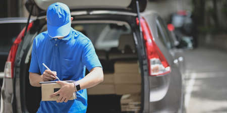 Professional delivery man working with parcel boxes, customer order in the car 写真素材
