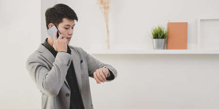 Professional businessman speaking on the phone while checking the time.