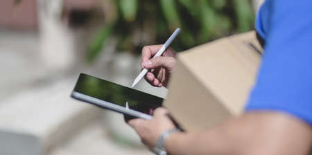 Close-up view of professional delivery man working with parcel box while checking customer order on tablet