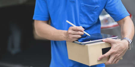 Cropped shot of delivery man preparing parcel box to customer while checking orders on tablet. 写真素材