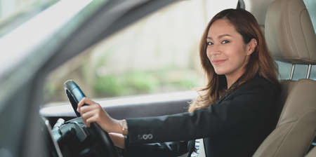 Professional businesswoman looking at the camera while driving the car to the office. Reklamní fotografie