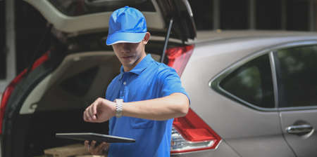 Young startup man checking the time and preparing orders for customers.
