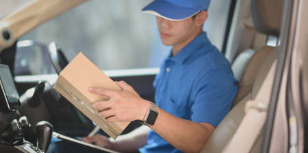 Young startup man checking orders for customers while sitting in the car preparing orders for shipping