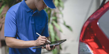 Delivery man checking orders on tablet, preparing the products to customers