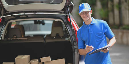 Delivery man checking orders for customer and smiling to the camera while standing in front of his car