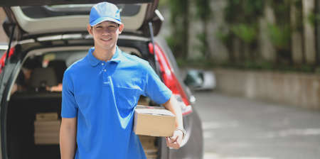 Delivery man preparing parcel box to customer and smiling to the camera while standing in front of his car