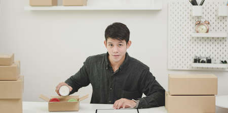 Young male small business owner checking orders and preparing the products for customers at home
