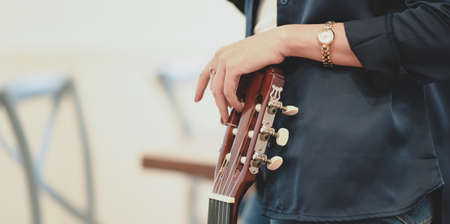 Close-up view of beautiful woman holding acoustic guitar in her free time at home.