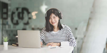 Young female freelancer working on her project with laptop computer while listening to her favourite music with headphones 스톡 콘텐츠