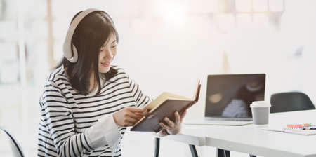 Young cheerful girl reading novels and listening to music in her free time at home