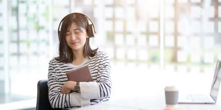 Young adorable female holding a book while listening to her favourite music in workplace 스톡 콘텐츠