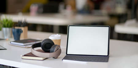 Modern workplace with blank screen tablet, on-ear headphones and office supplies on white table 版權商用圖片