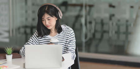 Young adorable female freelancer working on her project by writing her idea on notebook while listening to music 스톡 콘텐츠