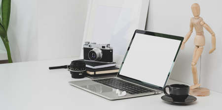 Minimal photographer workplace with open blank screen laptop and office supplies