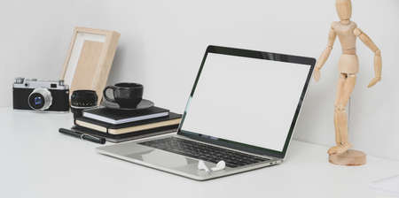 Professional photographer workplace with open blank screen laptop, camera and office supplies on white table 写真素材