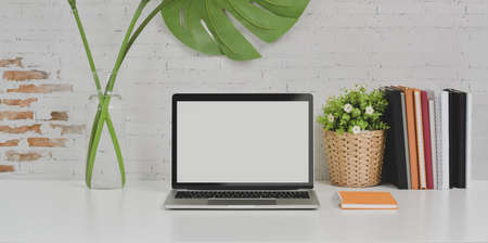 Comfortable designer workplace laptop computer and office supplies on white table with copy space