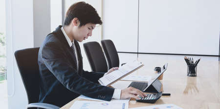 Male accountant analysing and reviewing expenditures for his company in the office room