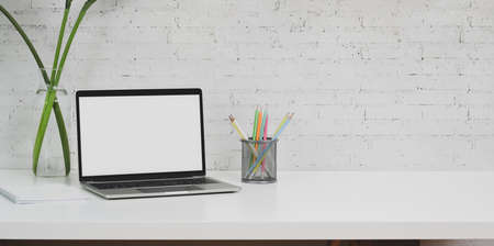 Minimal designer workplace with laptop computer and office supplies on white table with copy space