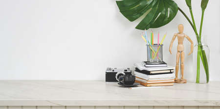 Minimal designer workplace with camera and office supplies on white table with copy space
