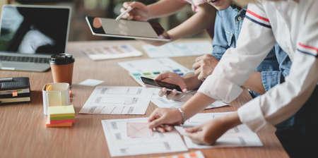 Équipe de jeunes graphistes professionnels de l'interface utilisateur discutant ensemble de leurs modèles de smartphones