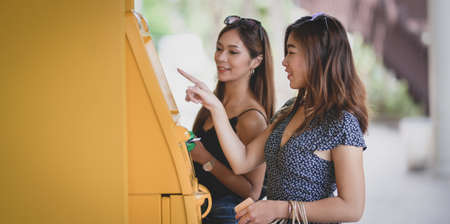 Two beautiful asian female withdrawing the money from a bank card using ATM machine at the mall