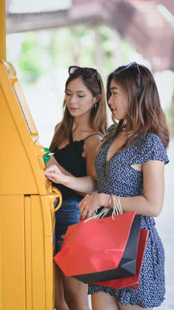 Two young asian female withdrawing the money from a bank card using ATM machine at the mall