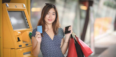 Portrait of beautiful asian woman holding credit card and shopping bags after withdrawing the cash from ATM machine