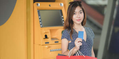 Portrait of beautiful asian woman holding credit card after withdrawing the cash from ATM machine