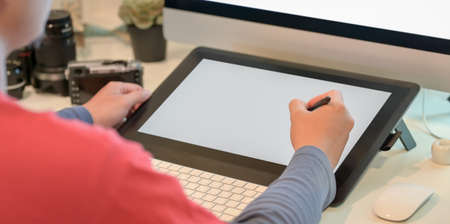 Close-up view of young male photographer retouching his images on digital tablet in his workplace
