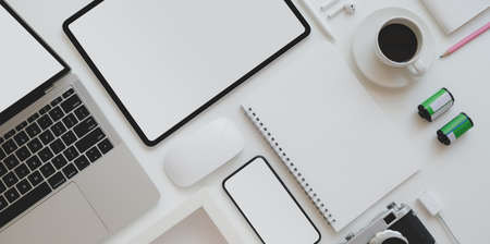 Top view of photographer workplace with blank screen tablet, laptop computer, vintage camera and office supplies on white table background