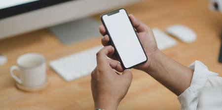 Close-up view of businessman holding blank screen smartphone in his modern office