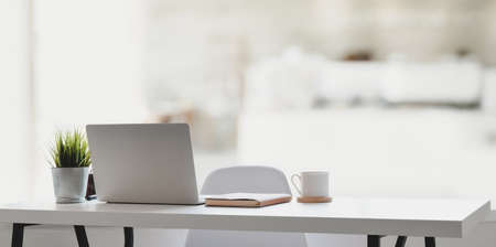 Comfortable workplace with laptop computer, coffee cup and office supplies with the relaxing atmosphere Stock Photo