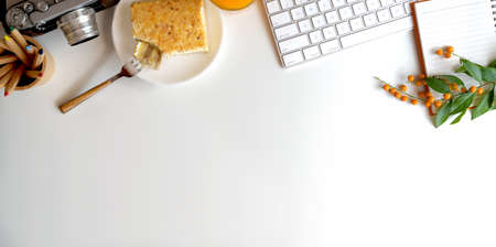 Top view of comfortable workspace with camera and breakfast on white table with copy space