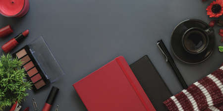 Top view of red luxury feminine workspace with copy space on dark grey desk background with make up and office supplies 写真素材